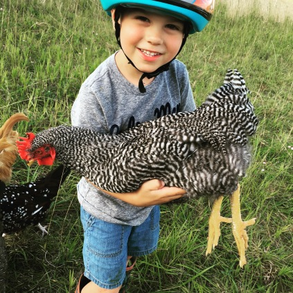Our oldest holding a chicken in a break from riding his bike.